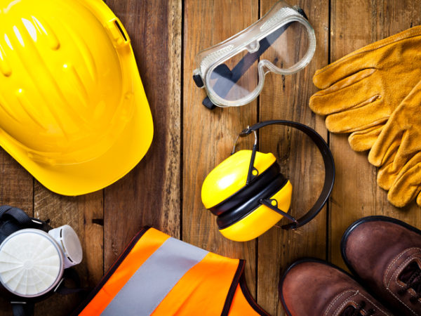Personal safety workwear items shot directly above. The safety equipment includes a hard hat, goggles, gloves, steel toe shoes, earmuff a respiratory mask and a safety vest. The background is a rustic wood table scratched and stained with vertical stripes.  Predominant colors are yellow and brown. DSRL studio photo taken with Canon EOS 5D Mk II
