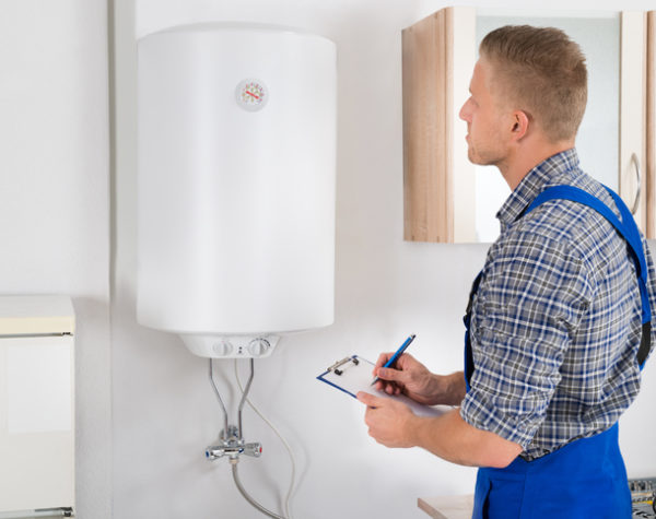 Young Man Writing On Clipboard While Looking At Electric Boiler